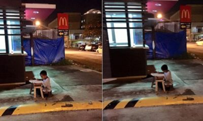 kid studying at sidewalk