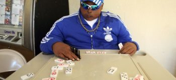 Dead Man Plays Dominoes At His Own Wake