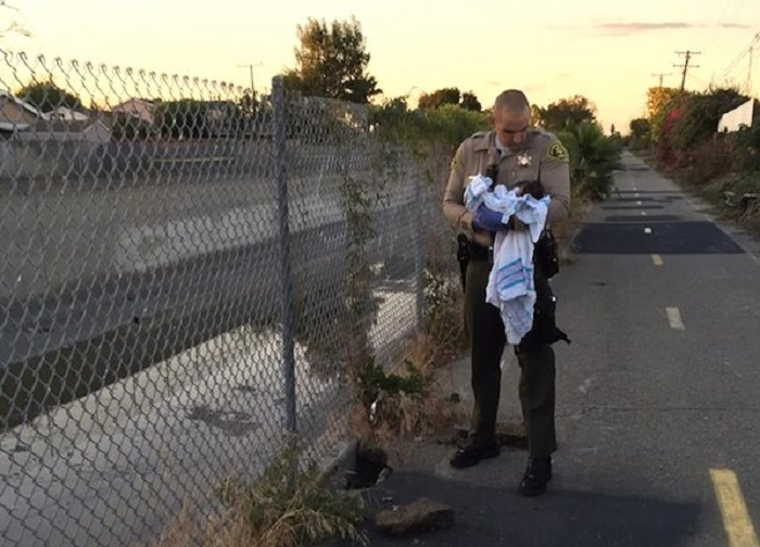 A newborn baby was found buried under asphalt and rubble near a riverbed.