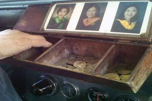 Photos of His College-Graduate Daughters Adorn a Jeepney Driver's Coin Holder