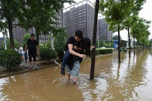 Woman Draws Mixed Reactions after Carrying Boyfriend through Flooded Streets