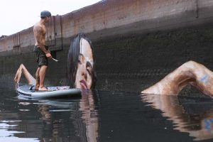 This Artist Creates Awesome Seaside Murals While Riding His Paddleboard