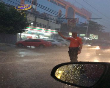 Las Piñas Traffic Enforcer Goes Viral for Doing Job Despite the Rain