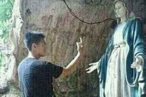 Guy Points Middle Finger at Statue of Virgin Mary