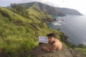 Son Sends Mom Vacation Photos, Holding a Sign to Assure Her He's OK