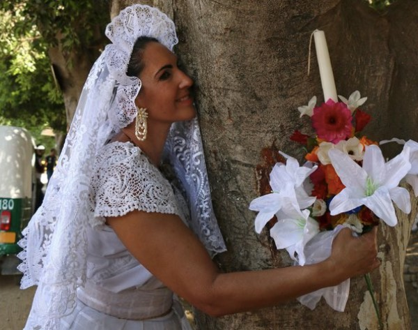 Dressed in white, these women got married to trees. [Image Credit: RT / Youtube]