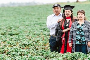 Woman Takes Photo in Field with Farmer Parents, Honors Their Sacrifices