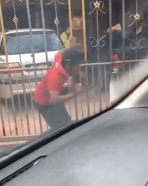 delivery man climbs gate
